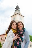 image of two women taking cell phone  - Travel tourists friends laughing taking photo with smartphone - JPG