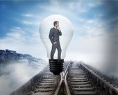 Thinking businessman in light bulb against railway tracks leading to clouds