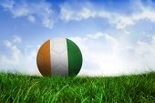 Football in ivory Coast colours on field of grass under blue sky