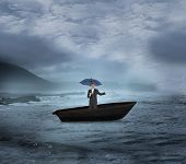 Composite image of peaceful businessman holding blue umbrella in a sailboat on open water