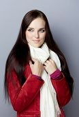 Portrait of a young smiling casual woman with long brunette hair on gray studio background, wearing