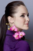 Portrait of a radiant young woman, with long brunette hair, on gray studio background, in purple top holding a purple silk orchid