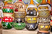 Variety of colorfully painted wooden flowers pots in market, Nairobi, Africa.