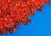 red plastic polymer granule product on blue