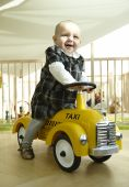 Smiling Baby Riding Toy Car