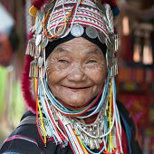 CHIANG RAI, THAILAND - DEC 4, 2013: Unidentified Akha tribe elderly woman in traditional clothes and silver jewelery smiles in hill tribe minority village. Northern thai cultural refugee population