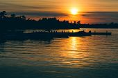 Sunset Over a Lake with Silhouetted Boats