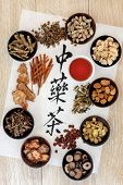 Chinese herbal tea selection and cup on rice paper over light oak wood. Translation of calligraphy s
