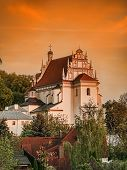 Historical Parish Church Fara in Kazimierz Dolny against sunset sky, Poland
