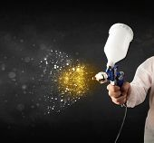 stock photo of airbrush  - Worker with airbrush painting with glowing golden paint and particles - JPG