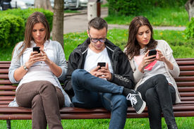 image of sitting a bench  - Group of friends two women and one man, sitting on a bench in park separately looking at their phones loosing communication. people using their phones and sending texts as they stand beside each other