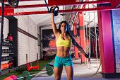 brunette girl at gym lifting a kettlebell weightlifting workout
