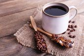 Mug of coffee on sackcloth on wooden background