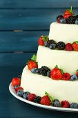 Beautiful wedding cake with berries on  dark wooden background