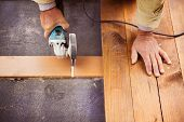 Carpenter grinding wooden planks