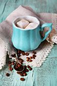 Cup of coffee with marshmallow and napkin on wooden table