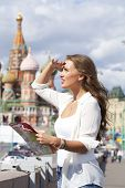 Young beautiful girl holding a tourist map of Moscow, Russia