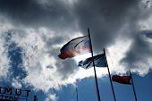 Russian flag on the wind against damatic clouds and flag of the Astrakhan region next