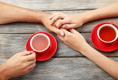Loving couple with hot drinks on table