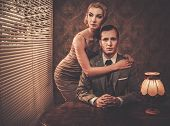 Well-dressed retro couple behind table
