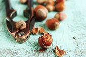 Hazelnuts and nutcracker on wooden background