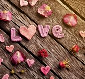 Word Love with rose petals and small heart shaped stuff on old vintage wood plates. Sweet holiday background.