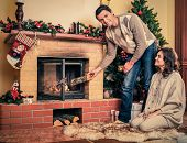 Couple putting log into  fireplace in Christmas decorated house interior