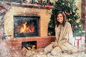 Young woman near fireplace in Christmas decorated house interior
