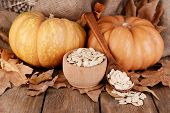 Pumpkins  and pumpkin seeds in bowl on wooden background
