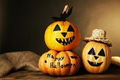 Halloween pumpkins on wooden table on dark color background