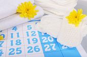 Sanitary pads and yellow flowers on blue calendar background