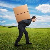 tired young businessman carrying two heavy boxes on the field
