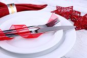 White plates, knife, fork, napkin and Christmas decoration on wooden background