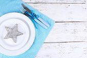 White plates, fork, knife and Christmas decoration on blue polka dot napkin on wooden background