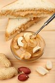 Creamy peanut butter in bowl and bread slices on wooden table