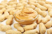 Creamy peanut butter in bowl on peanut background, close-up