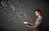 image of sketch book  - Young man reading a book while hand drawn sketches coming out of the book - JPG