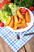 Homemade fried potato on plate on wooden background