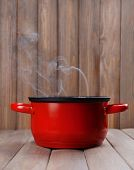 Cooking pot with steam on table on wooden background