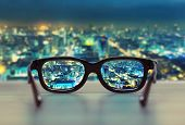 stock photo of protective eyewear  - Night cityscape focused in glasses lenses - JPG