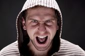 stock photo of bitchy  - Portrait of young angry screaming man with a hood - JPG