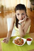 Young beautiful woman eating italian pasta with tomatoes, parmezan and basil.