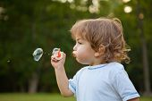Little boy blowing soap bubbles in park