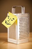 Drawn smiley face on a post-it note sticked on a grater