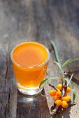 image of sea-buckthorn  - Sea buckthorn juice and berries isolated on wooden background - JPG