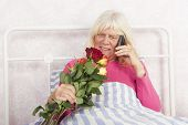 image of pyjama  - Happy woman in pink pyjama sitting in bed with roses and talking on the phone - JPG