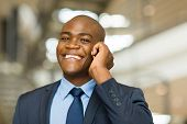 cheerful african american businessman talking on cell phone
