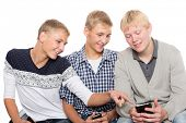 Young men use smartphones and sitting on the couch. Two of the boys twin brothers.