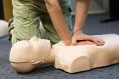 picture of cpr  - A group of adult education students practitcing CPR chest compressioon on a dummy - JPG