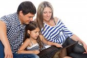 Family sitting on a rug and using a laptop. Isolated on white.